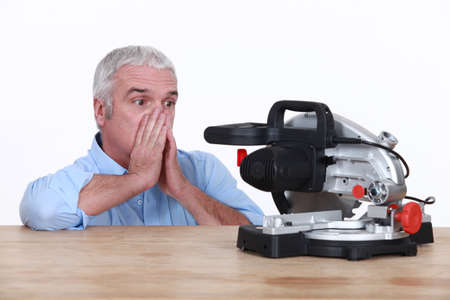 disarray: Mature looking at his circular saw with disarray Stock Photo