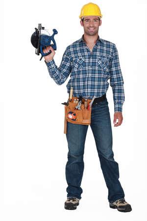 flannel: Tradesman holding a circular saw