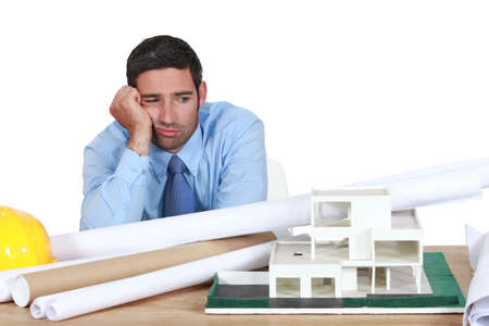 confused person: Bored architect sat at desk
