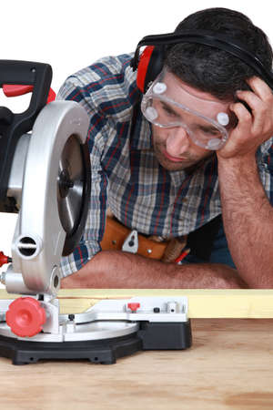 figuring: Man figuring out how to use saw