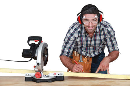 sawhorse: Man with band saw marking wood Stock Photo