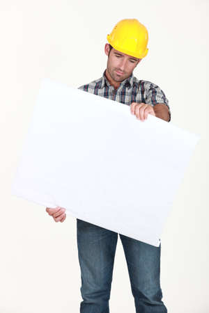 banter: Workers examining white plate Stock Photo