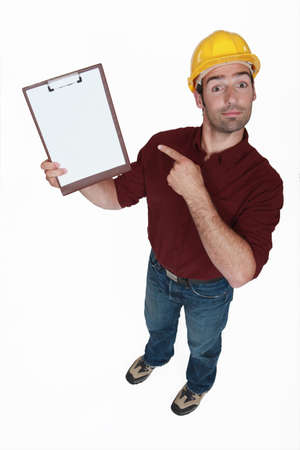 jobsite: Construction worker pointing at his clipboard.