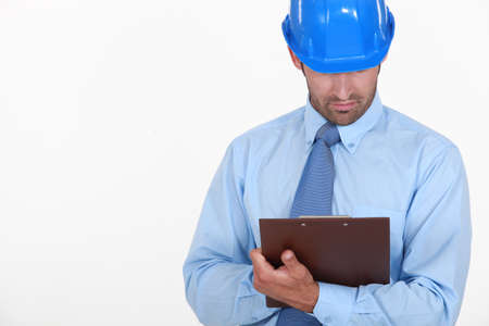 Businessman in a hardhat with a clipboard