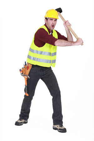whack: Construction worker smashing with a sledgehammer Stock Photo