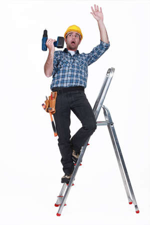 perforate: craftsman falling off a ladder Stock Photo