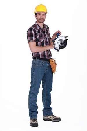 Worker holding circular saw photo