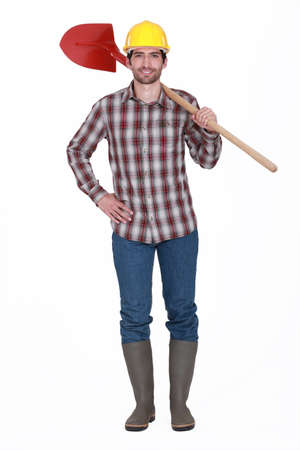 wellington: bricklayer standing against white background holding red shovel Stock Photo