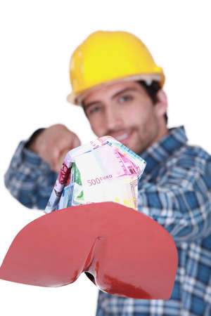 lucrative: Laborer with a shovel full of bills Stock Photo