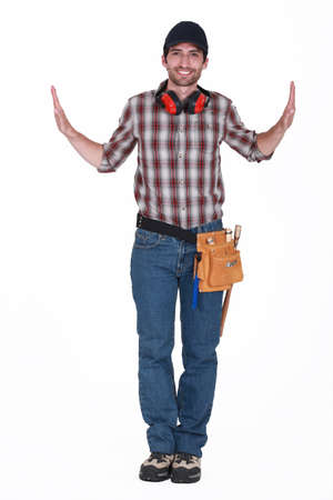 either: portrait of handsome carpenter wearing cap with hands raised on either side Stock Photo