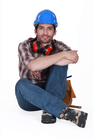 autonomic: Craftsman with a helmet and earplugs sitting on the floor