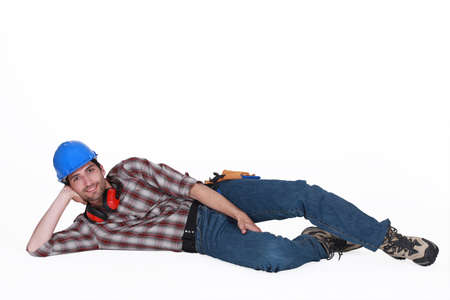 unconcerned: Tradesman lying on the ground Stock Photo