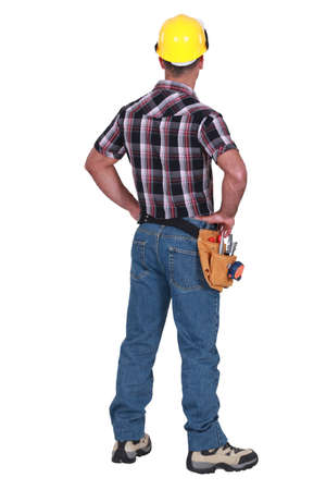 Laborer standing on white background, back-view photo