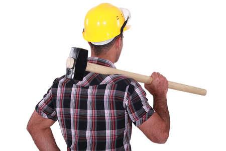 sledge hammer: Man carrying sledge-hammer over shoulder
