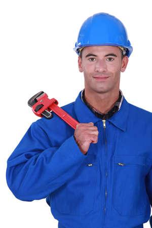 jumpsuit: portrait of electrician holding adjustable spanner