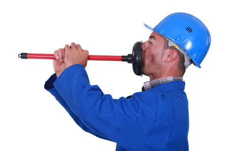 unplugging: Plumber unplugging his mouth.