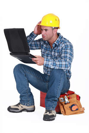 Confused builder sat with laptop photo