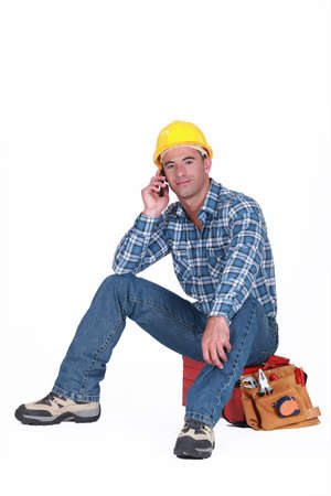 yellow shirt: young tradesman on the phone with customer Stock Photo