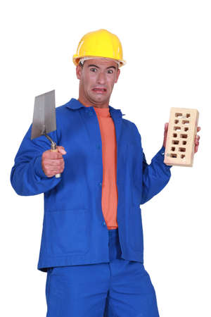 repulsive: mason holding a trowel and a brick and looking disgusted