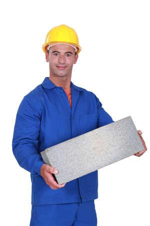 stonemasonry: Tradesman carrying a cinder block Stock Photo