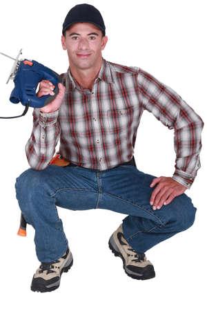 Handyman holding a jigsaw photo