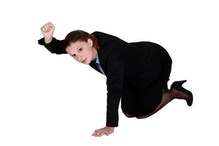 Businesswoman kneeling on the floor and holding up her fist photo