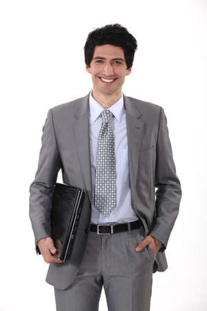 preppy: portrait of handsome young businessman all smiles with laptop Stock Photo