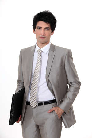 black pants: Businessman walking with his hand in his pocket and holding his laptop Stock Photo