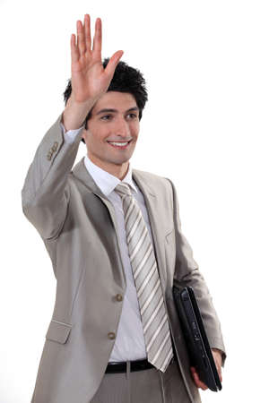 A businessman waving to someone. photo