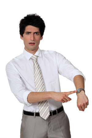 molesto: Hombre de negocios enojado señalando su reloj