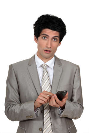 wrinkled brow: Wide-eyed businessman sending a text message