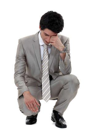 kneeled: A sad businessman.