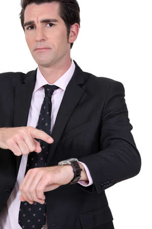angry boss: Angry boss pointing at watch