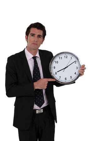 arrive: Man pointing at clock Stock Photo