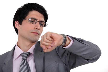 looking at watch: A businessman checking the time, Stock Photo