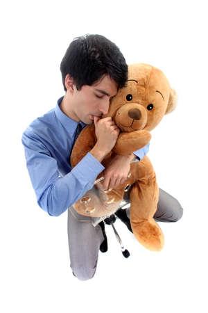 suck: A businessman hugging a teddy bear. Stock Photo