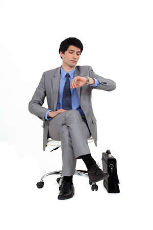 gray suit: Seated businessman looking at his watch Stock Photo