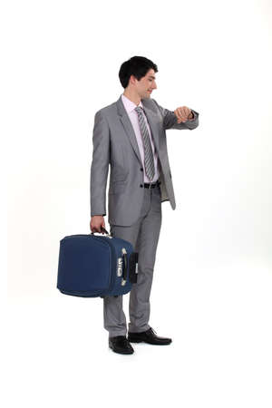 suit case: businessman with luggage consulting his watch Stock Photo