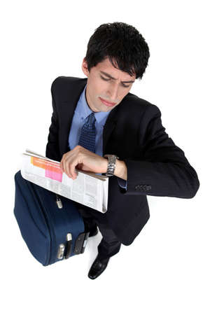 late thirties: Businessman with a case looking at his watch Stock Photo