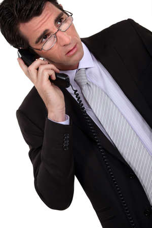 uneasiness: Concerned businessman talking on the phone Stock Photo