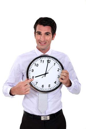 punctual: hombre de negocios feliz apuntando al reloj Foto de archivo