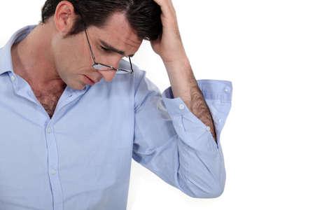 cansancio: joven empresario busca cansado con gafas bajar y mano a la cabeza