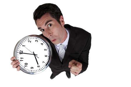 admonester: Tir � angle �lev� d'un homme d'affaires tenant une horloge