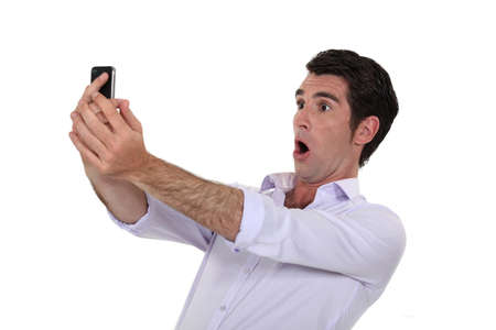 amazement: Man surprised watching his mobile phone