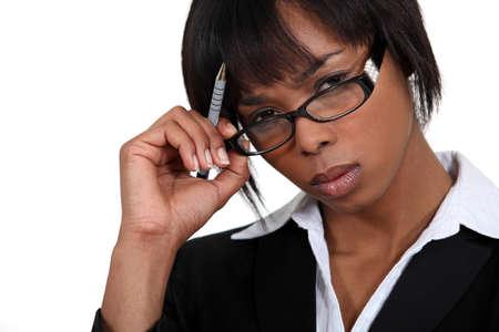 exacting: Stern businesswoman touching her glasses Stock Photo