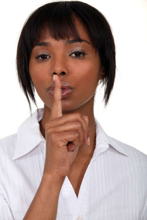reprimanding: Woman holding her index finger to her lips