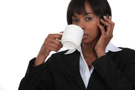 Businesswoman drinking coffee whilst on the phone photo