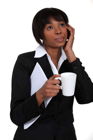 Businesswoman telephoning whilst holding coffee mug and documents photo
