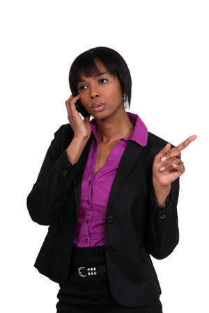 beautiful black woman on the phone pointing sideways photo