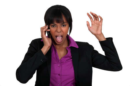frustration girl: A black businesswoman furious over the phone.